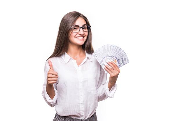 Mujer de negocios con cabello largo castaño en ropa casual tiene muchos billetes de dólar sobre blanco