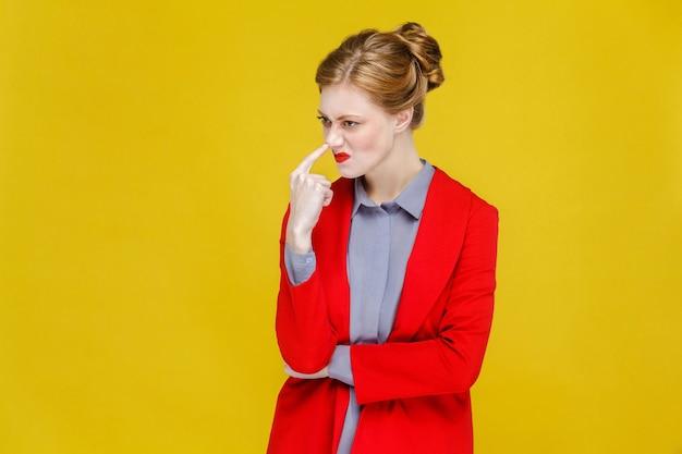 Mujer de negocios de cabeza roja jengibre en traje rojo mostrando signo extraño mentiroso