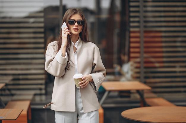 Mujer de negocios en un café tomando café, usando el teléfono