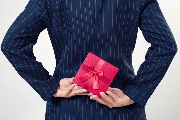 Mujer de negocios con una caja de regalo a la espalda