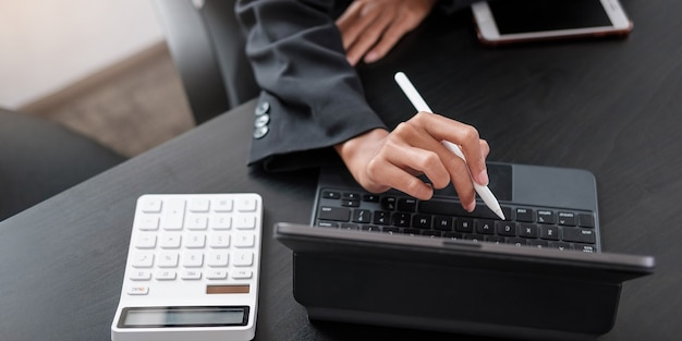 Mujer de negocios con calculadora para hacer finanzas matemáticas en un escritorio de madera en la oficina y el fondo de trabajo empresarial, impuestos, contabilidad, estadísticas y concepto de investigación analítica