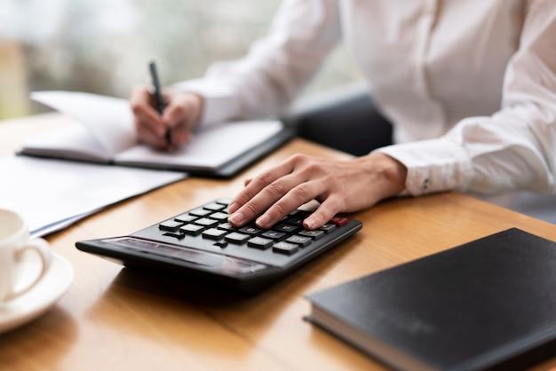 Mujer de negocios calculando y escribiendo