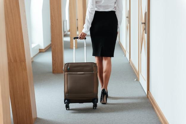 Mujer de negocios caminando con maleta a lo largo del pasillo del hotel