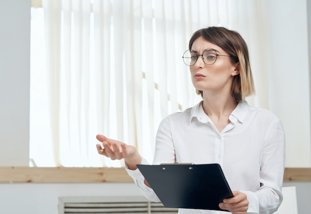 Mujer de negocios en camisa blanca con carpeta en manos para papeles de oficina