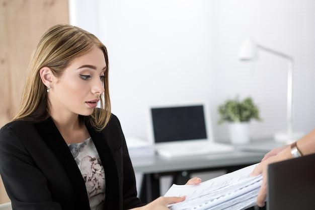 Mujer de negocios cansada obteniendo nuevo montón de documentos. exceso de trabajo, horas extraordinarias y estrés en el concepto de trabajo.