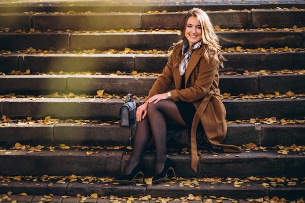 Mujer de negocios en la capa que se sienta en las escaleras