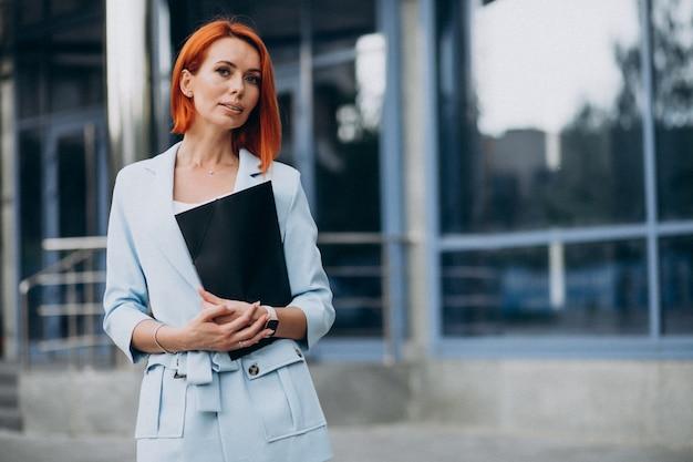 Mujer de negocios con carpeta por el centro de la oficina