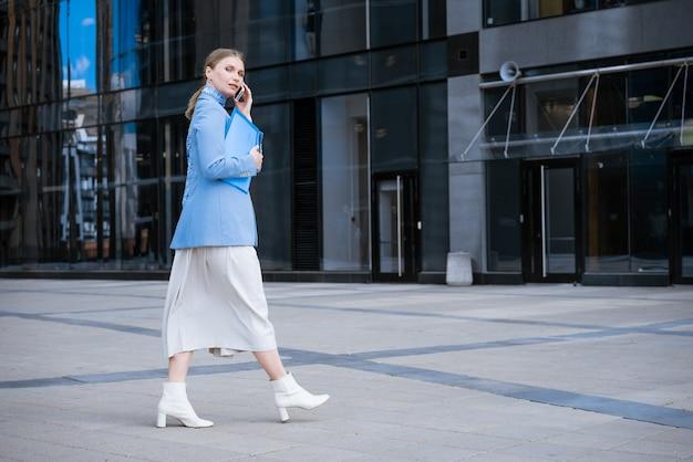 Mujer de negocios caucásica en una chaqueta azul y vestido hablando por teléfono con una carpeta de papeles en la mano contra la pared de un edificio de oficinas
