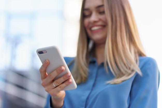 Mujer de negocios caucásica hablando por teléfono con café para llevar. una mujer europea exitosa, hablando por teléfono, de pie en el edificio de oficinas moderno