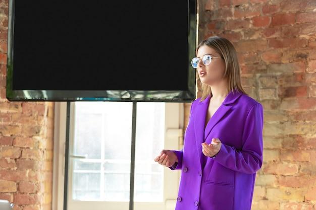Mujer de negocios caucásica joven que trabaja en la oficina, parece elegante. papeleo, analizando