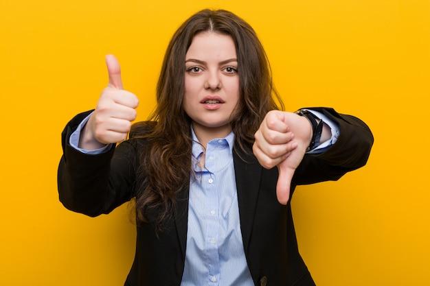 Mujer de negocios caucásica de talla grande joven que muestra los pulgares hacia arriba y hacia abajo, difícil elegir el concepto
