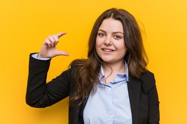 Mujer de negocios caucásica de talla grande joven sosteniendo algo pequeño con los dedos índices