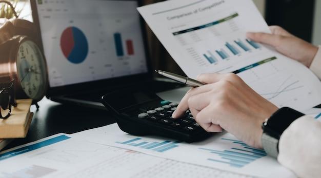 Mujer de negocios de cerca con calculadora y computadora portátil para hacer finanzas matemáticas en el escritorio de madera en la oficina y el concepto de trabajo de negocios, impuestos, contabilidad, estadísticas e investigación analítica
