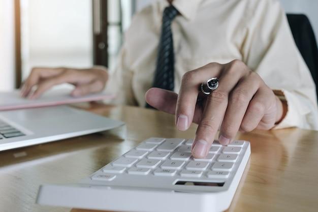 Mujer de negocios de cerca con calculadora y computadora portátil para hacer finanzas matemáticas en el escritorio de madera en la oficina y el fondo de trabajo empresarial estadísticas de contabilidad fiscal y concepto de investigación analítica