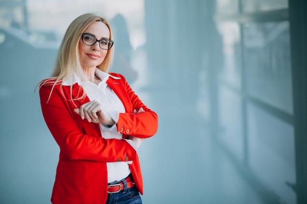 Mujer de negocios en chaqueta roja aislada en oficina