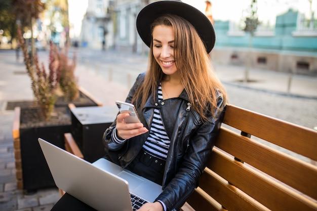 Mujer de negocios de chica estudiante sentarse en un banco de madera en la ciudad en el parque en otoño