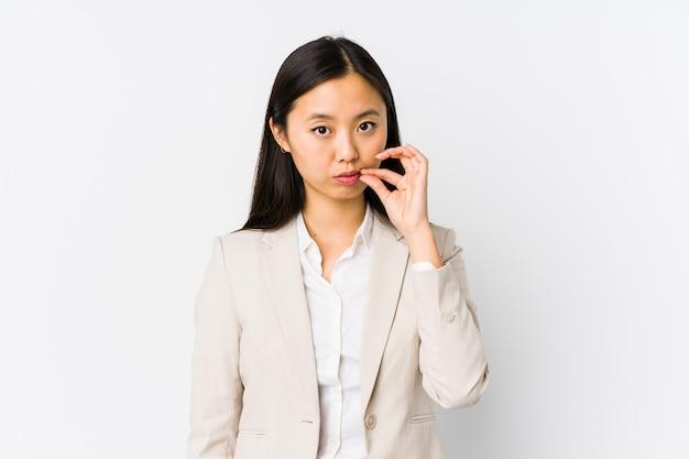 Mujer de negocios china joven aislada con los dedos en los labios que guardan un secreto.