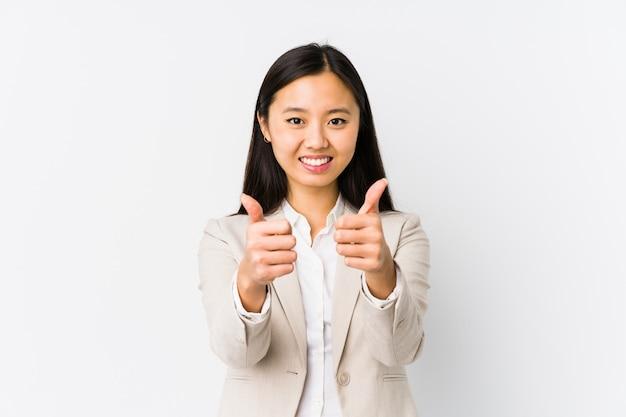 La mujer de negocios china joven aislada con los pulgares sube, anima sobre algo, apoya y respeta el concepto.