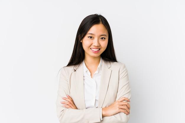 Mujer de negocios china joven aislada que se siente confiada, cruzando los brazos con determinación.