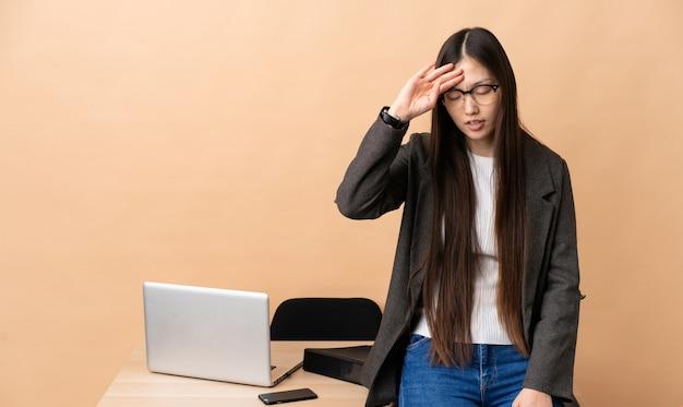 Mujer de negocios chinos en su lugar de trabajo con expresión cansada y enferma