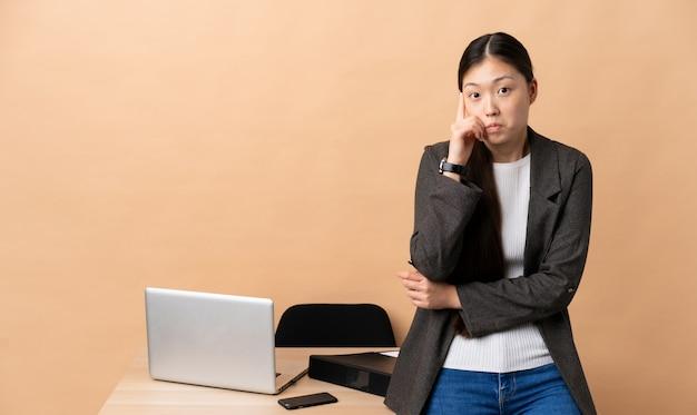 Mujer de negocios chinos en su lugar de trabajo pensando en una idea