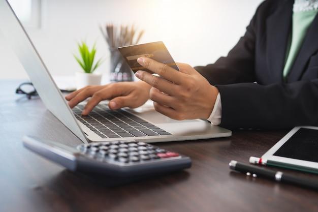 La mujer de negocios completa la tarjeta de crédito en la computadora portátil para pagar y comprar, internet y la tendencia de pago digital