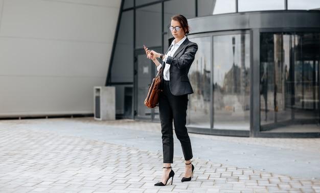 Una mujer de negocios comprueba la hora en la ciudad durante una jornada laboral esperando una reunión