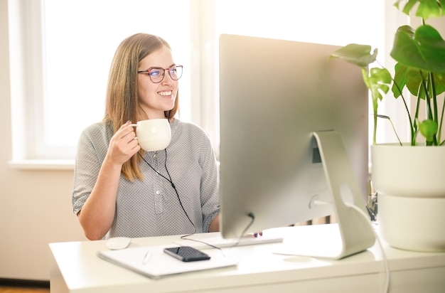 Mujer de negocios con computadora en casa, oficina, taza de café.