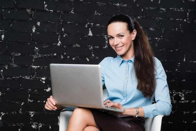 Mujer de negocios en la computadora portátil en una oficina moderna de loft