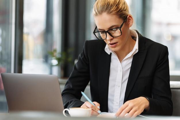 Mujer de negocios concentrada escribiendo notas en el cuaderno.