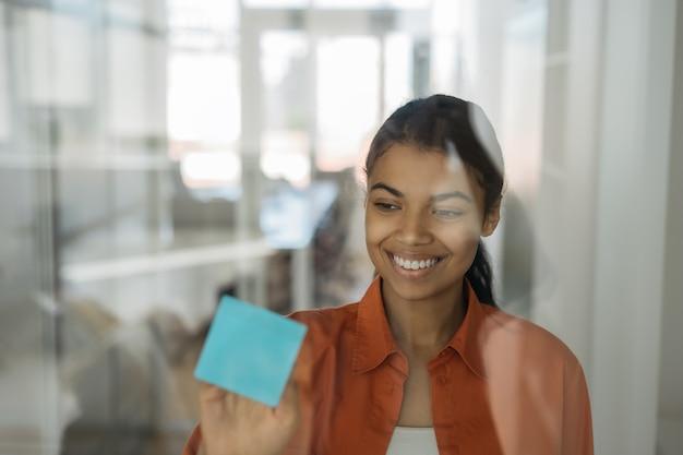 Mujer de negocios confiada que trabaja en la oficina moderna, planificación de la puesta en marcha, usando scrum