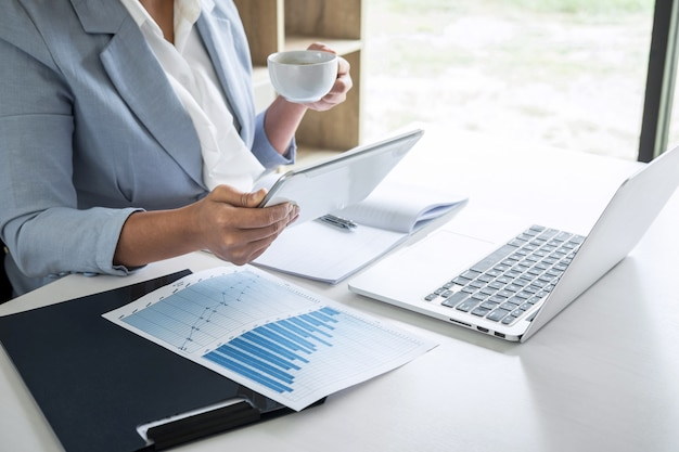 Mujer de negocios contable financiero trabajando auditoría y cálculo de gastos informe financiero anual balance general, haciendo documento de verificación de finanzas y tomando notas en papel de informe