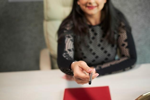 Mujer de negocios dando pluma