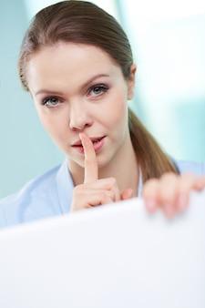 Mujer de negocios con el dedo en los labios