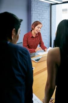 Mujer de negocios discutiendo estadísticas con compañero de trabajo
