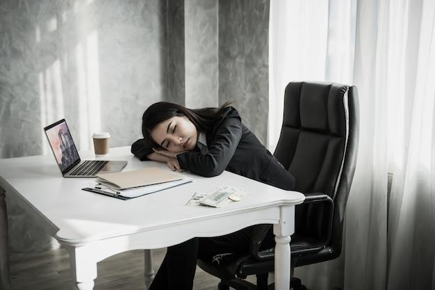Mujer de negocios dormir en el lugar de trabajo de escritorio después de un trabajo cansado duro.