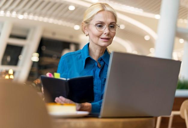 Mujer de negocios de edad avanzada con gafas escribiendo en la agenda y mirando portátil