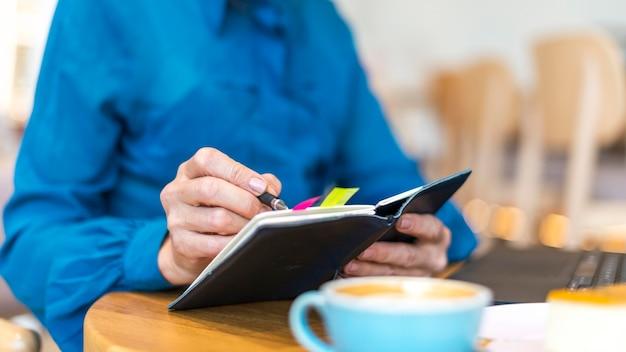 Mujer de negocios de edad avanzada que trabaja en la computadora portátil y escribiendo en la agenda