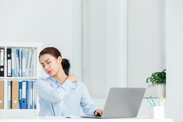 Mujer de negocios ejecutiva dolor de hombro en una oficina