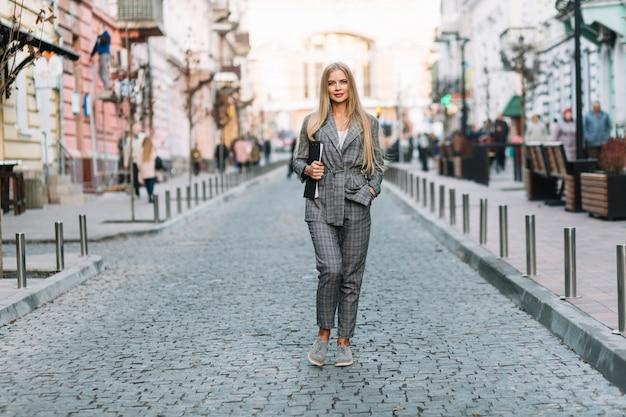 Mujer de negocios elegante andando en ciudad con portapapeles
