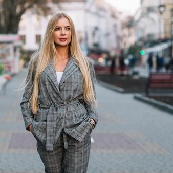 Mujer de negocios elegante andando en ciudad