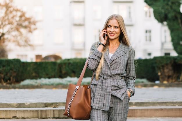 Mujer de negocios elegante haciendo llamada en ciudad