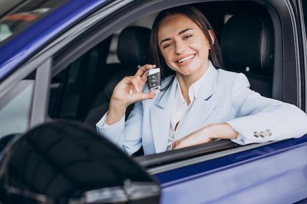 Mujer de negocios eligiendo un coche en una sala de exposición de coches