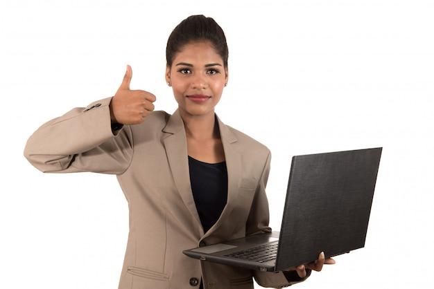 Mujer de negocios emocionada feliz que sostiene la computadora portátil y que muestra los pulgares para arriba aislados en un espacio en blanco