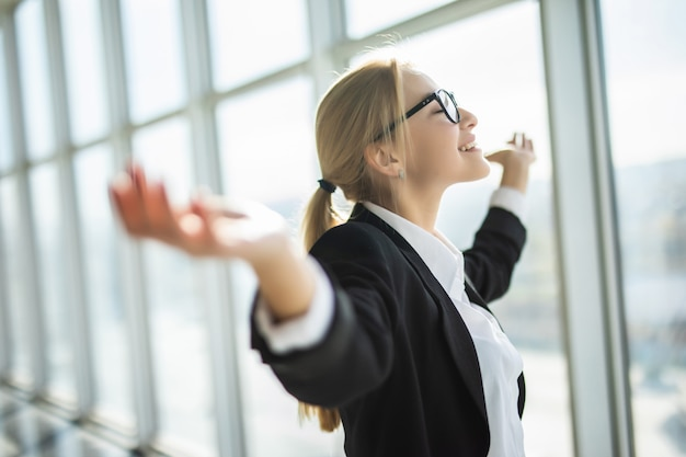 Mujer de negocios emocionada sostenga las manos levantadas los brazos celebrar la victoria en la oficina moderna