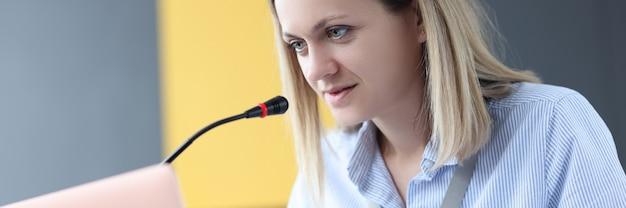 Mujer de negocios emplazamiento en la computadora portátil y micrófono parlante.