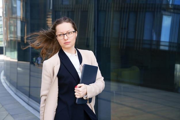 Una mujer de negocios se encuentra con una computadora portátil en un traje y gafas fuera de un edificio de oficinas durante el día.