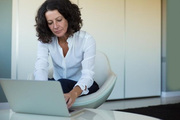 Mujer de negocios enfocada trabajando mientras espera socios