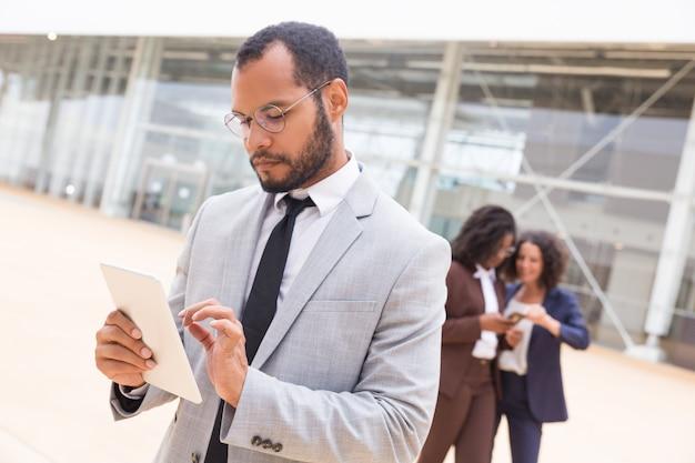 Mujer de negocios enfocada usando tableta afuera