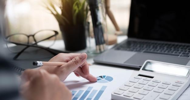 Mujer de negocios de enfoque suave usando una calculadora para calcular los números en la mesa de trabajo